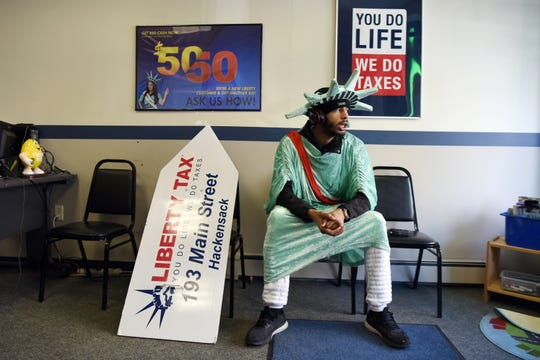 Alexander Jeremy Bernard, 21, takes a break from dancing to South African music while wearing a Statue of Liberty costume on Main Street in Hackensack on March 12, 2019. For the last four years during tax season, Bernard has been a fixture on the street, bringing attention to Liberty Tax, a tax preparation business.