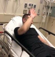 In this still image taken from a video provided by the U.S. Attorney's Office, a man in a hospital bed raises his arm over his face after being hit by former Paterson cop Ruben McAusland.