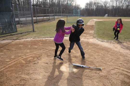 Cayden Walsh wants to play on the girls softball team. Here he practices with his father and sisters.