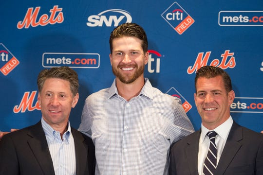 New York Mets pitcher Jacob deGrom, center, Mets COO Jeff Wilpon, left, and Executive Vice President and General Manager Brodie Van Wagenen, pose during a baseball news conference Wednesday, March 27, 2019, in Arlington, Va.  The Cy Young Award winner and the Mets agreed to a $137.5 million, five-year contract, on Monday, March 25, a deal that includes $52.5 million deferred into the 2030s. (AP Photo/Cliff Owen)