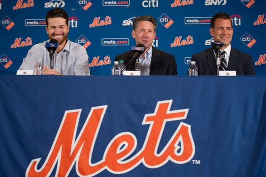 New York Mets pitcher Jacob deGrom, left, Mets COO Jeff Wilpon, center, and Executive Vice President and General Manager Brodie Van Wagenen, speak during a baseball news conference Wednesday, March 27, 2019, in Arlington, Va.  The Cy Young Award winner and the Mets agreed to a $137.5 million, five-year contract, on Monday, March 25, a deal that includes $52.5 million deferred into the 2030s. (AP Photo/Cliff Owen)