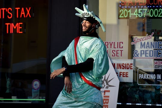 Alexander Jeremy Bernard, 21, dances to South African music while wearing a Statue of Liberty costume on Main Street in Hackensack on March 12, 2019. For the last four years, during tax season, Bernard has been a fixture on the street, bringing attention to Liberty Tax, a tax preparation business.