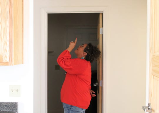 Teri Silversmith, a senior development coordinator for Navajo Housing Authority, examines a door frame on Tuesday inside a house the agency recently renovated in Newcomb.