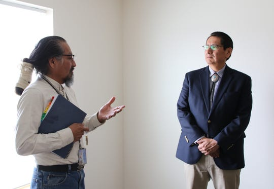 From left, Earl Tulley, veterans liaison for Navajo Housing Authority, talks to Navajo Nation President Jonathan Nez about the agency's home modernization program.