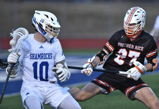 Catholic Central varsity lacrosse player Patrick Lee, left, tries to get around Brother Rice defender Trevor Fix.