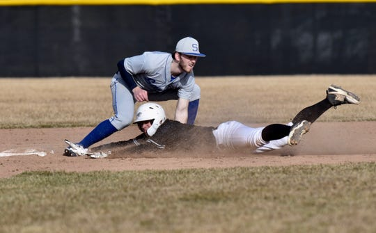 Plymouth's Nick Koski is tagged out while attempting to steal second base by Salem's Jacob Amato on March 27, 2019.