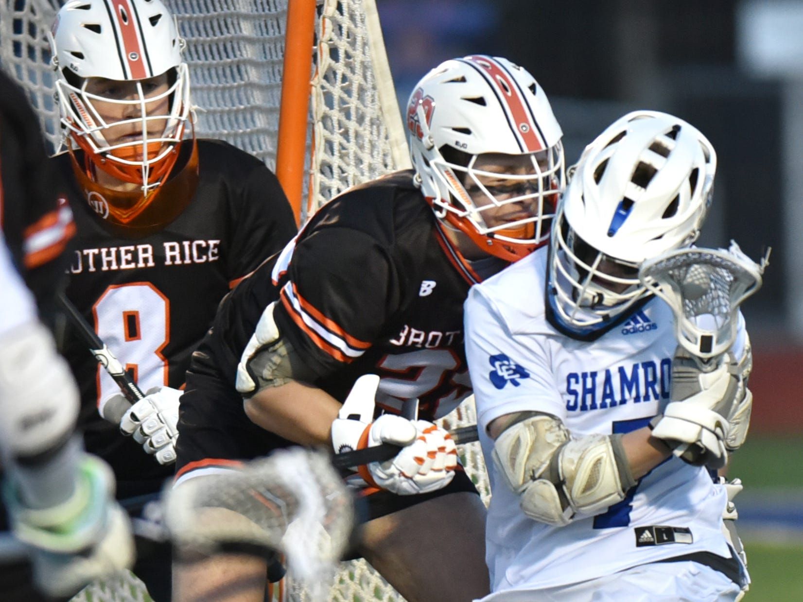 As Brother Rice net-minder Dom Dababbo (#8) keeps an eye on the action, Catholic Central's Ryan Sullivan gets crunched by a cross-check by Rice's Jack Lockwood.