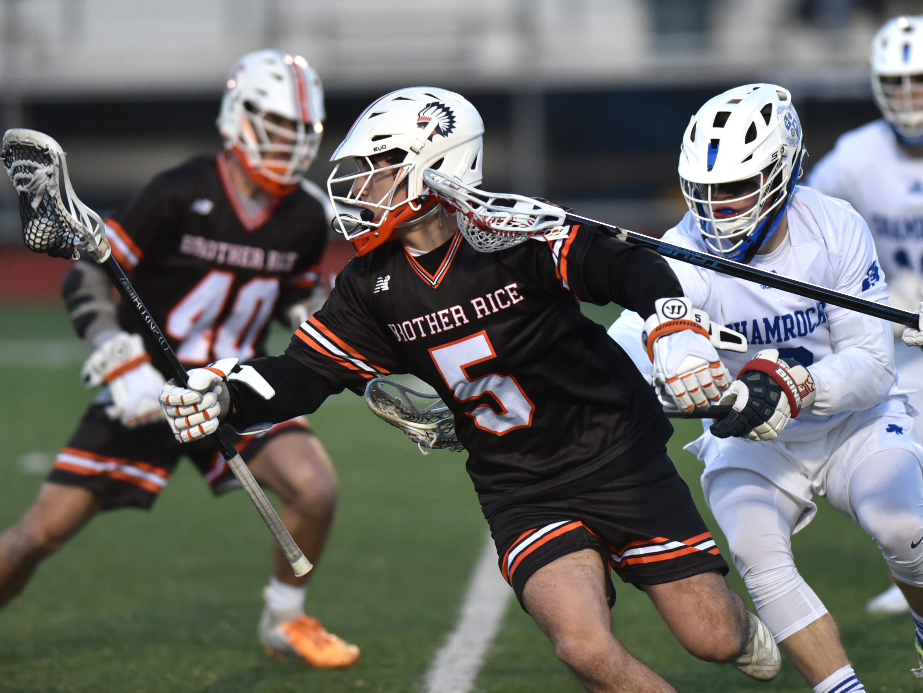 Birmingham Brother Rice player Dylan Braddock plays keep-away from two pursuing CC players.