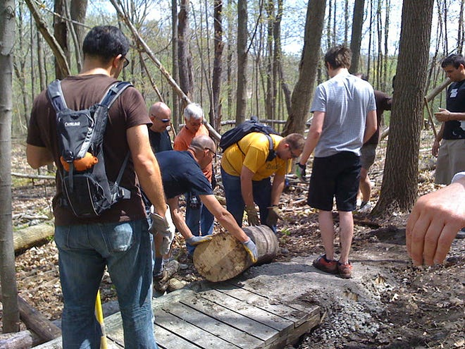 Members of the Motor City Mountain Biking Association clear a path for a bike trail.