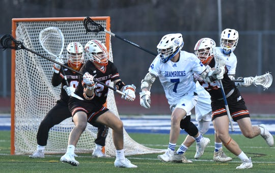 Catholic Central Shamrock Ryan Sullivan tries to sneak in front of the Brother Rice goal as he's watched by Jack Lockwood, center.