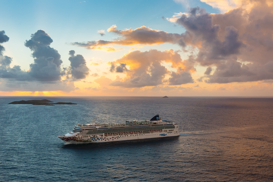 The Norwegian Cruise Line sails the ocean with the sun setting behind