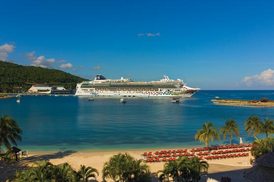 The Norwegian Cruise Line docked near a beautiful sandy beach