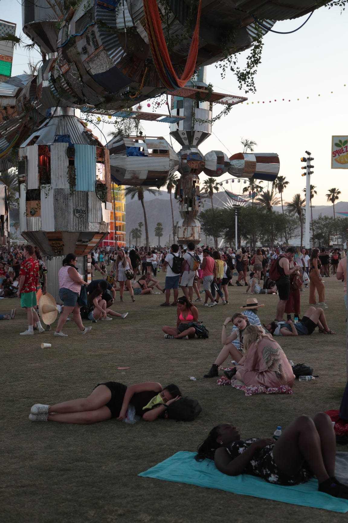 Festivalgoers relax underneath the Palm-3 World Station at the Coachella Valley Music and Arts Festival at the Empire Polo Club in Indio, Calif., April 22, 2018.