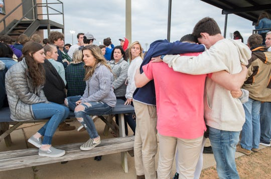 Students mourn the death of senior pitcher Connor Wood (#16) prior to the Marianna vs Gulf Breeze baseball game at Gulf Breeze High School on Tuesday, March 26, 2019.  Wood died on Sunday.