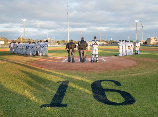 Players stand in a moment of silence for Dolphins senior pitcher Connor Wood (#16) prior to the Marianna vs Gulf Breeze baseball game at Gulf Breeze High School on Tuesday, March 26, 2019.  Wood died on Sunday.