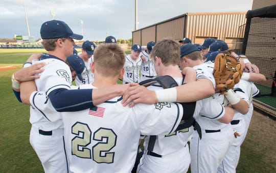 Teammates huddle to remember senior pitcher Connor Wood (#16) prior to the Marianna vs Gulf Breeze baseball game at Gulf Breeze High School on Tuesday, March 26, 2019.  Wood died on Sunday.