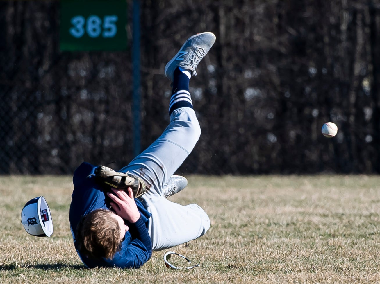 A Dallastown outfielder loses his hat and sunglasses after making a diving attempt at a catch during a YAIAA baseball game against Gettysburg on Wednesday, March 27, 2019.