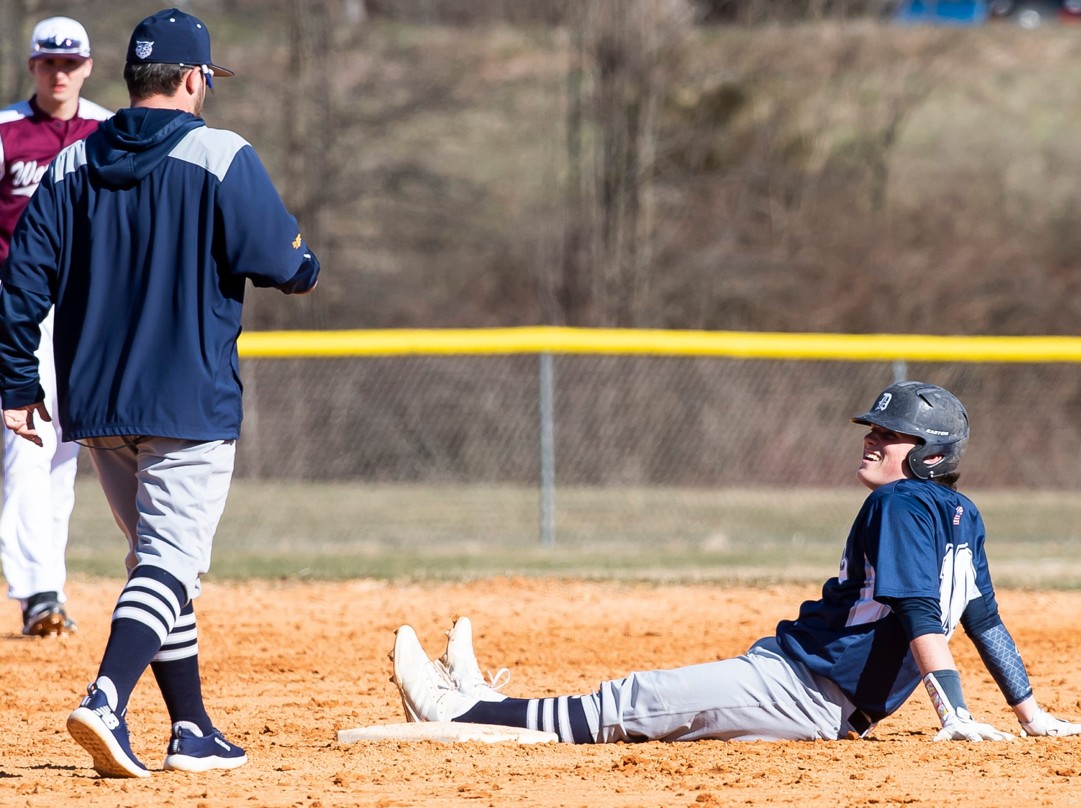 Dallastown's Julian Bailey smiles on second base as a coach checks on him after suffering a minor injury during a YAIAA baseball game against Gettysburg on Wednesday, March 27, 2019.