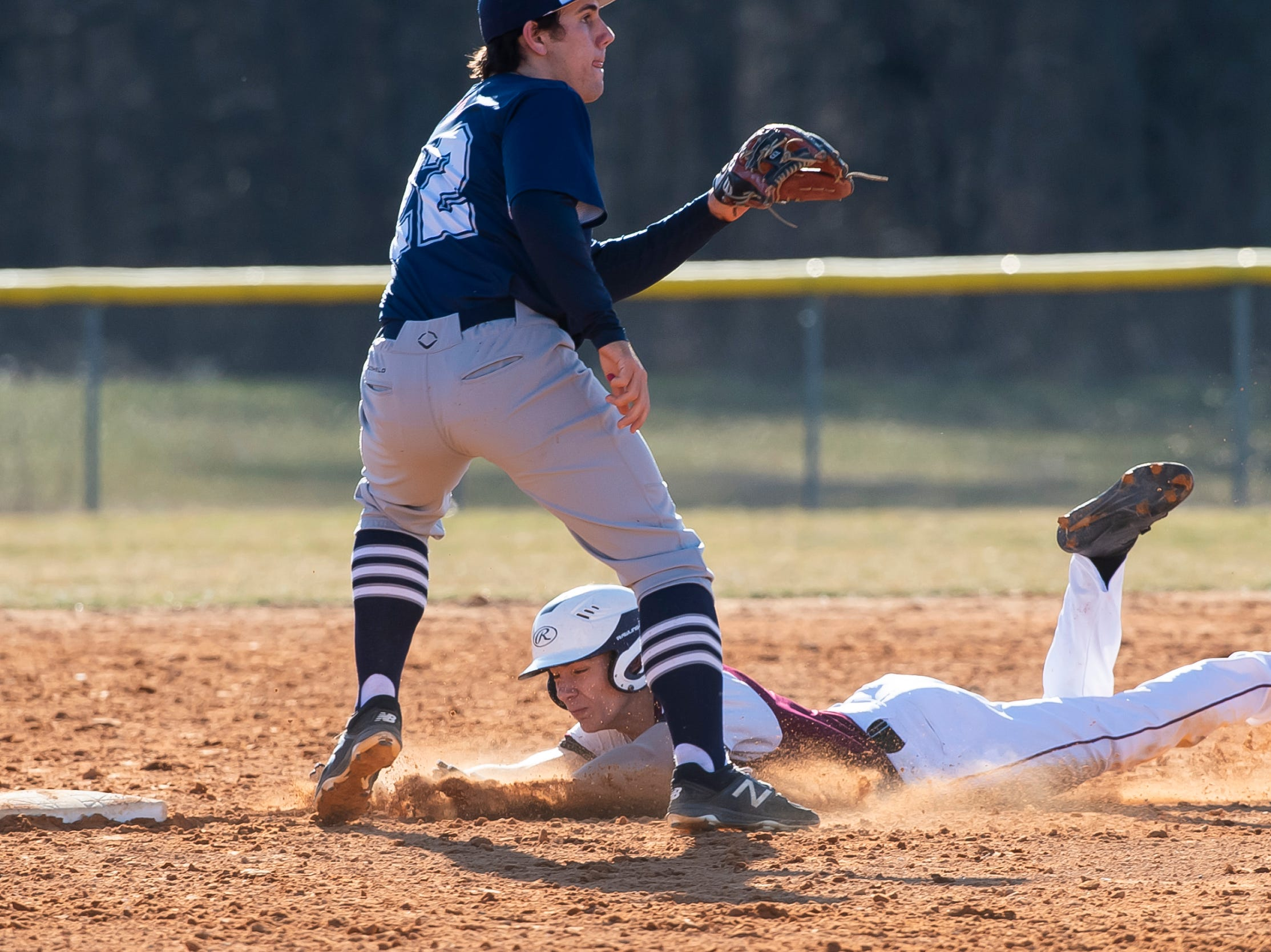Gettysburg's Dillon Gebler safely slides head-first into second base during a YAIAA baseball game against Dallastown on Wednesday, March 27, 2019.