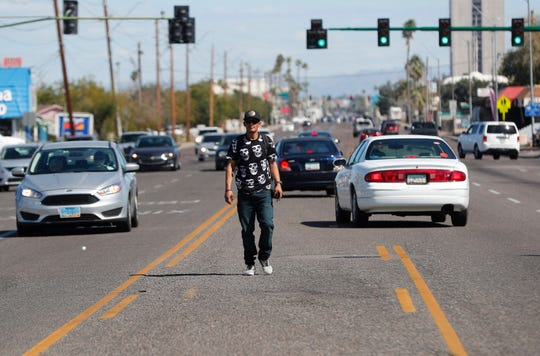 A pedestrian walks in the center lane while crossing Indian School Road west of 19th Avenue in Phoenix on March 10, 2019.