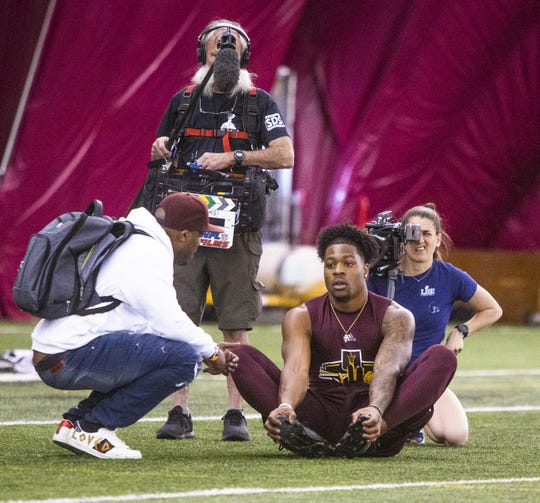 Former Arizona State University wide receiver N'Keal Harry stretches while an NFL Films crew shoots him as he talks with someone at the 2019 Football Pro Day held on campus, Wednesday, March 27, 2019.