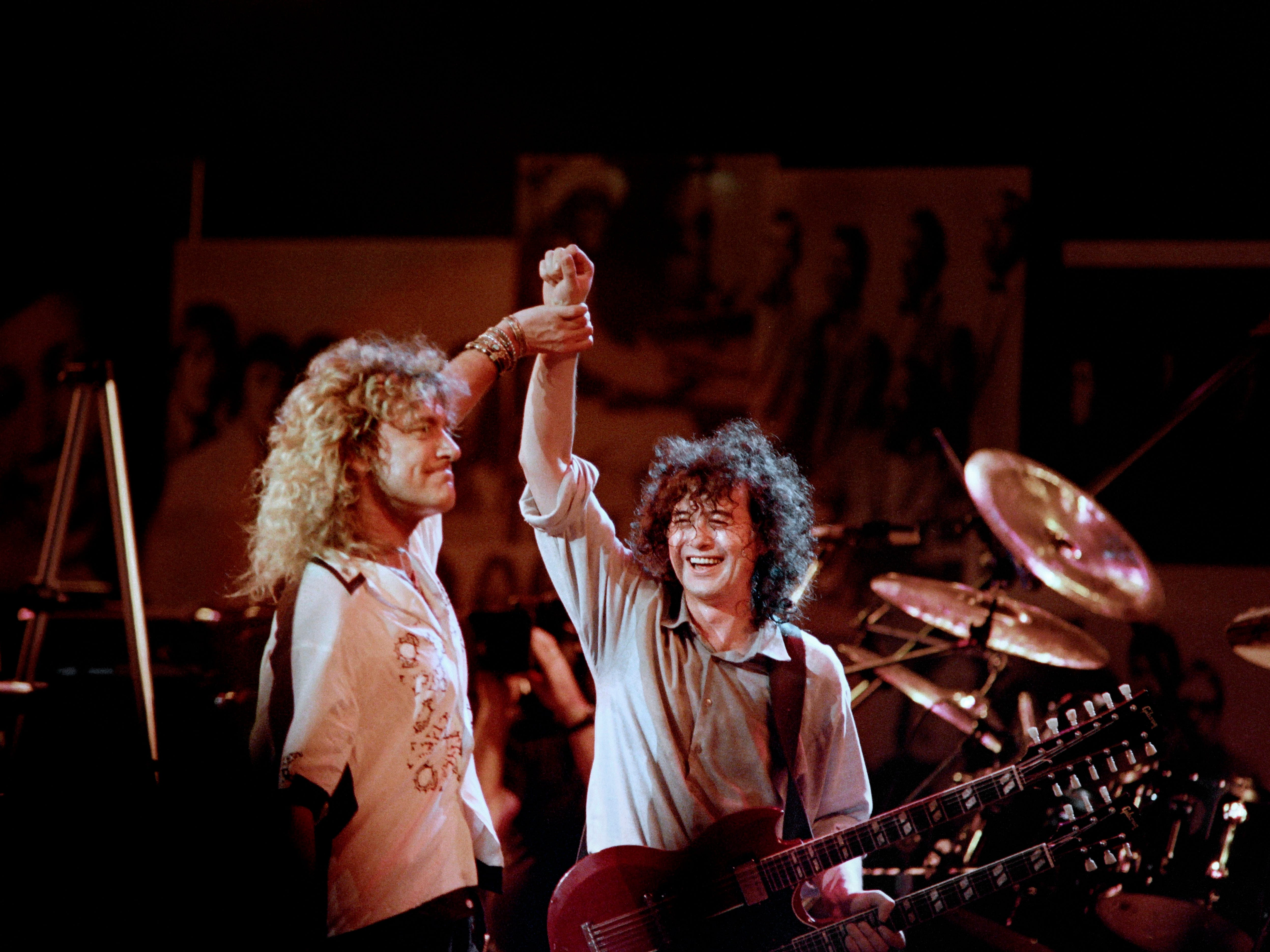 Robert Plant (L) holds hands raised high with Jimmy Page during a Led Zeppelin reunion performance at Madison Square Garden in New-York on May 14, 1988.