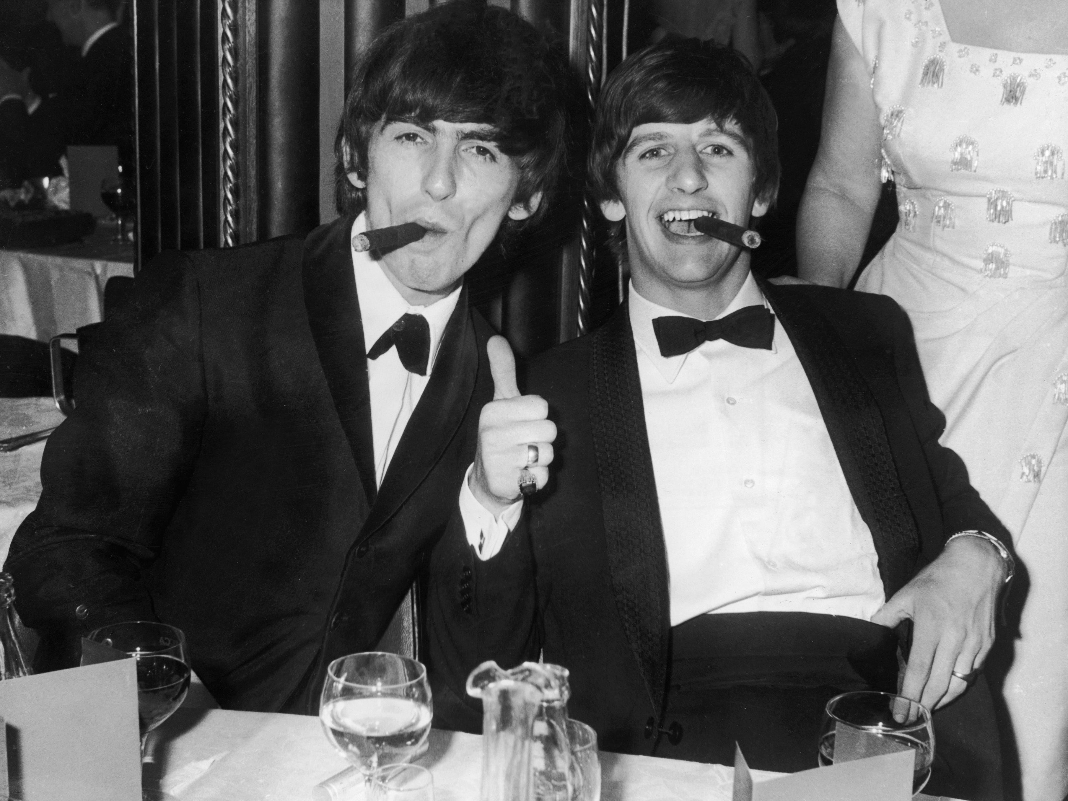 George Harrison and Ringo Starr smoke cigars in tuxedos after the presentation of the Carl Allen Awards March 23, 1964 in London.