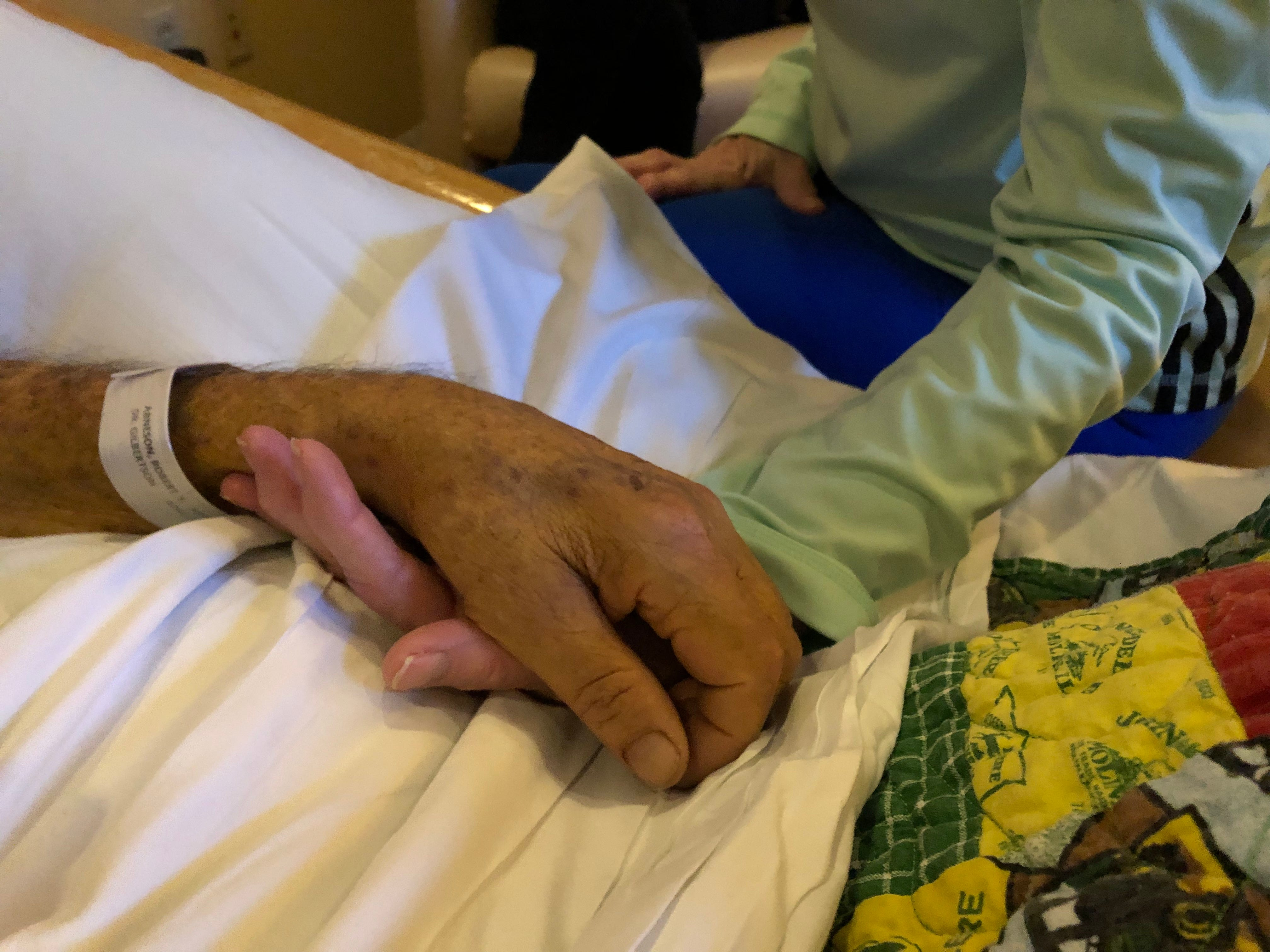 Jeannie Crotty, who's volunteered as an 11th Hour Companion for about four years, slips her hand under patient Robert Arneson's. Though Robert couldn't hear or see her, Jeannie swore she felt him squeeze her hand.