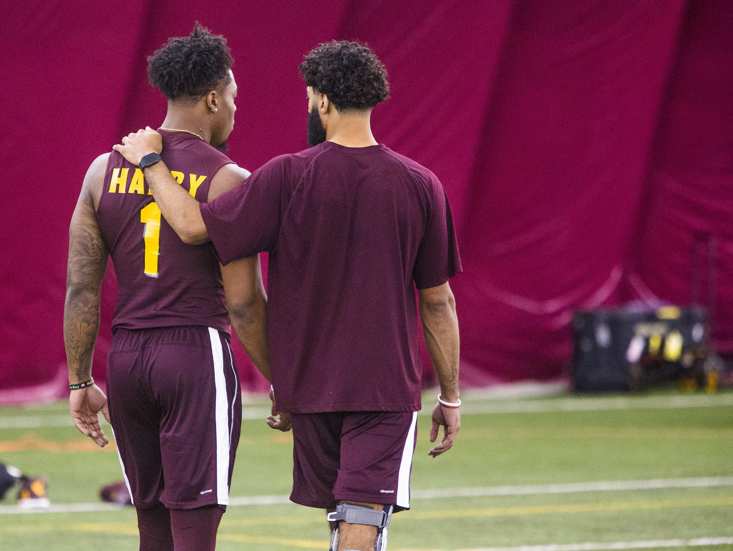 Former Arizona State University wide receiver N'Keal Harry and quarterback Manny Wilkins, Jr., right, share a private moment at the 2019 Football Pro Day held on campus, Wednesday, March 27, 2019.