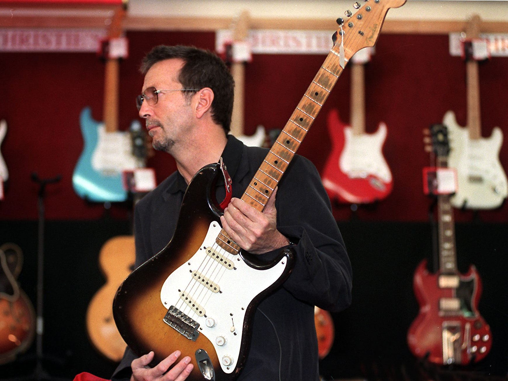 "Eric Clapton poses at Christie's in 1999 with his 1956 Fender Stratocaster guitar (which he used on the albums ""Just One Night,"" ""Backless"" and ""Slowhand"") in front of a selection of his guitars that went under the hammer in New York to raise money for a drug and alcohol rehabilitation centre in the Caribbean island of Antigua."
