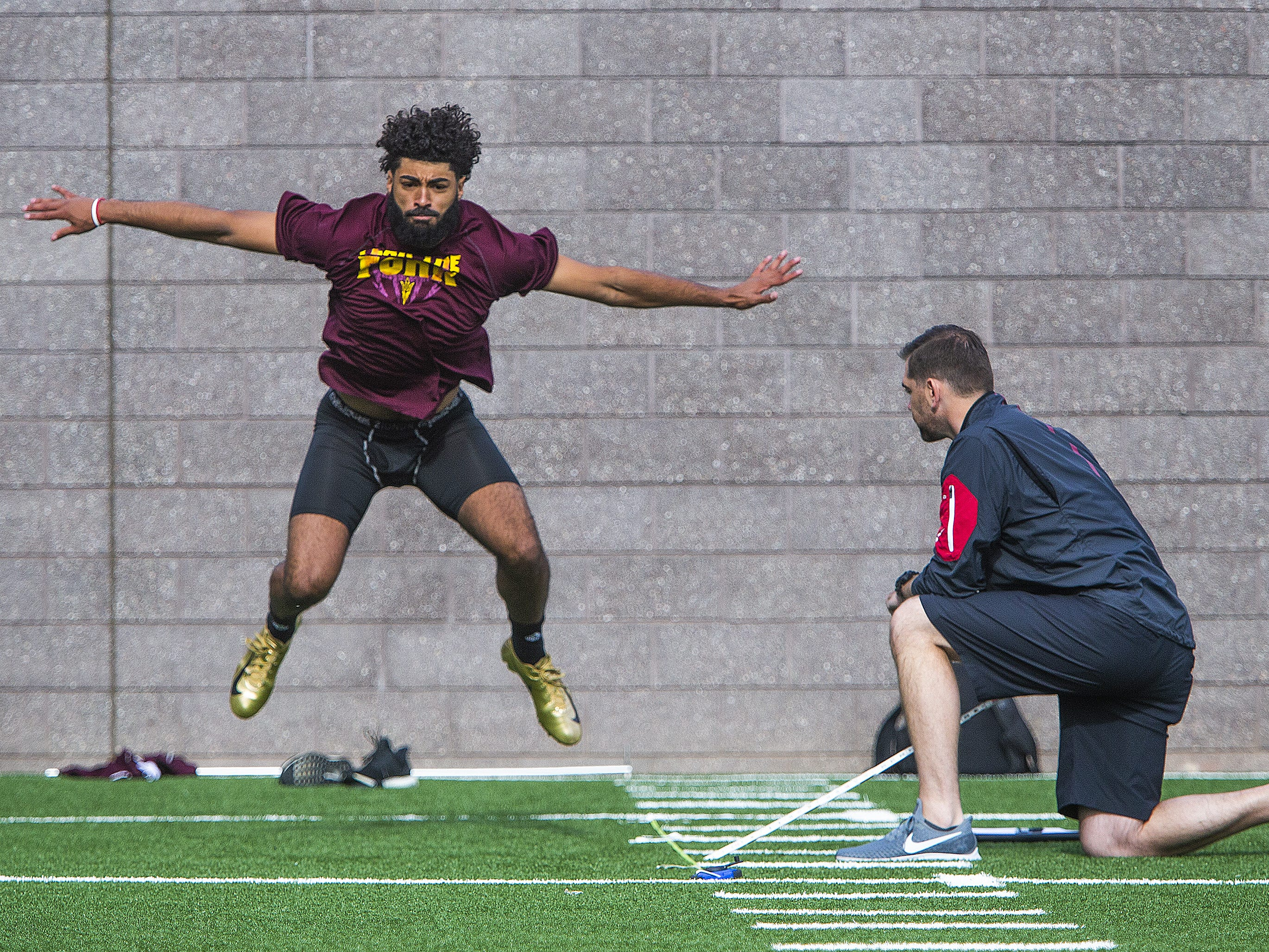 Former Arizona State University quarterback Manny Wilkins, Jr., does the standing broad jump at the 2019 Football Pro Day held on campus, Wednesday, March 27, 2019.