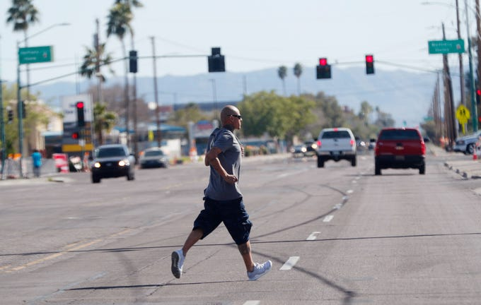 A pedestrian crosses 27th Avenue north of Bethany Home Road in Phoenix on March 10, 2019.
