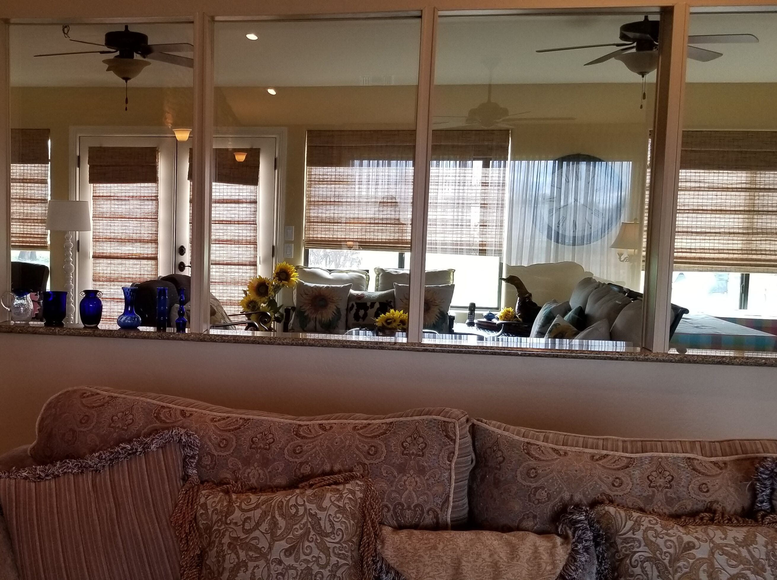 A patio was enclosed to create an Arizona room. A pony wall topped by glass panels separate the sun room and living room.