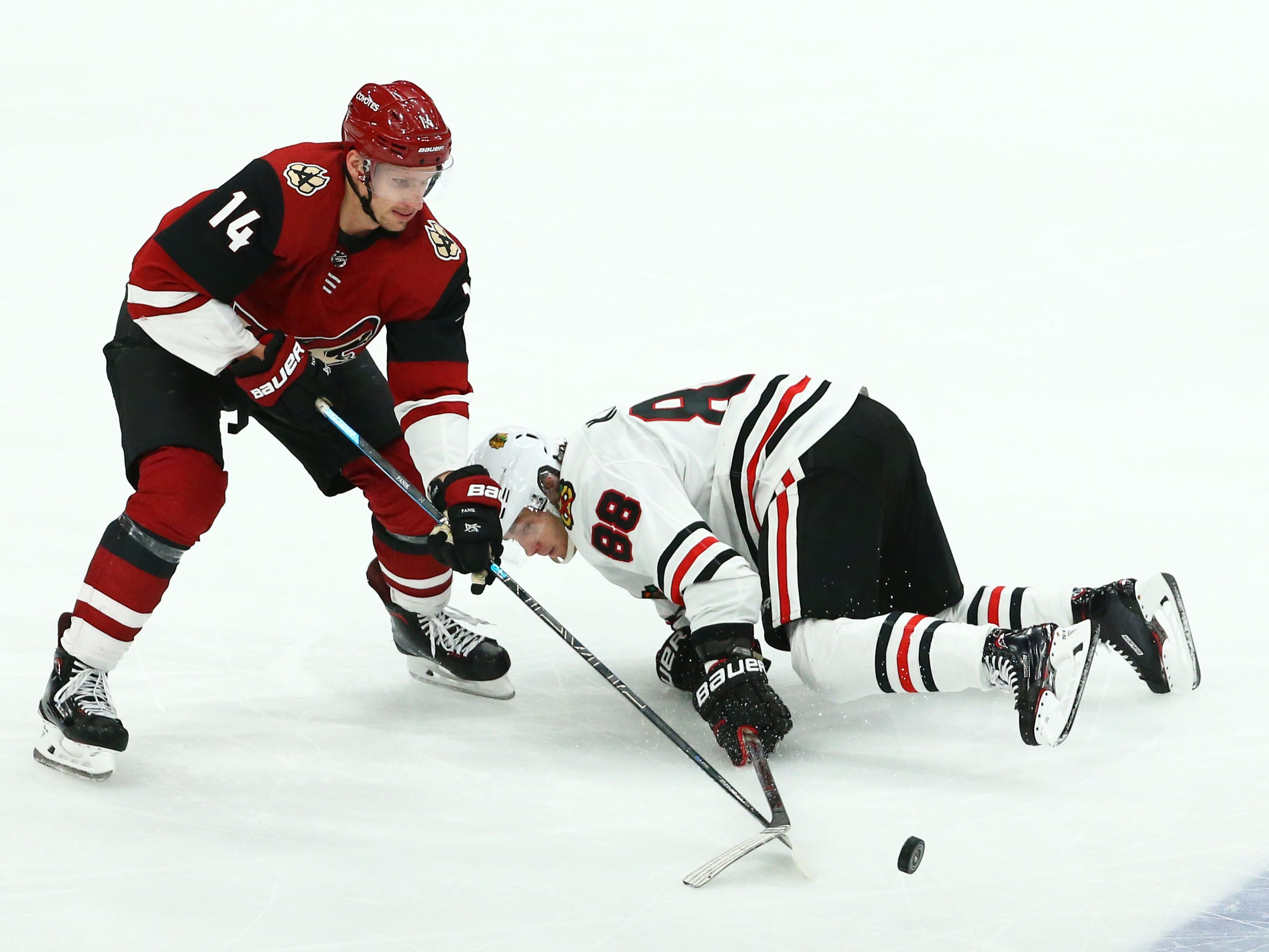 Arizona Coyotes right wing Richard Panik (14) battles with Chicago Blackhawks right wing Patrick Kane (88) in the third period on Mar. 26, 2019, at Gila River Arena in Glendale, Ariz.