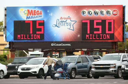 A billboard at 44th Street and McDowell Road in Phoenix, Ariz. displays the jackpots for Mega Millions and Powerball on Mar. 27, 2019.