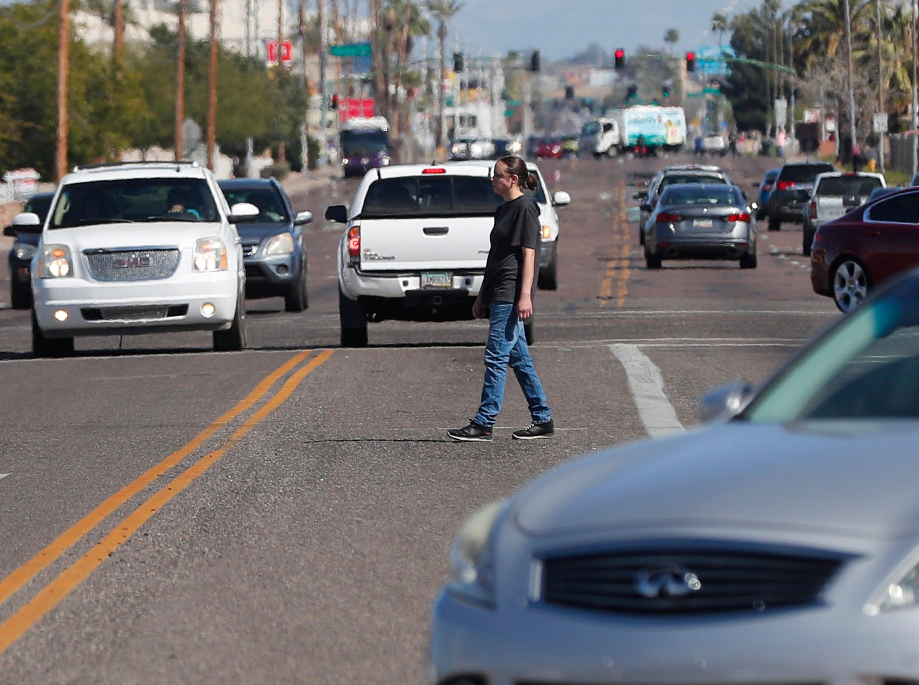 A pedestrian crosses Indian School Road, west of 19th Avenue in Phoenix on March 10, 2019.