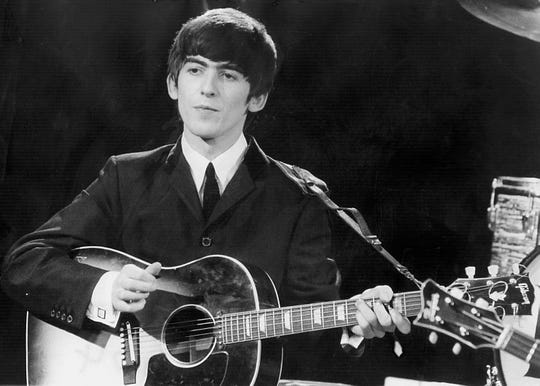 Beatles guitarist and singer George Harrison performs December 3, 1963 during a concert.