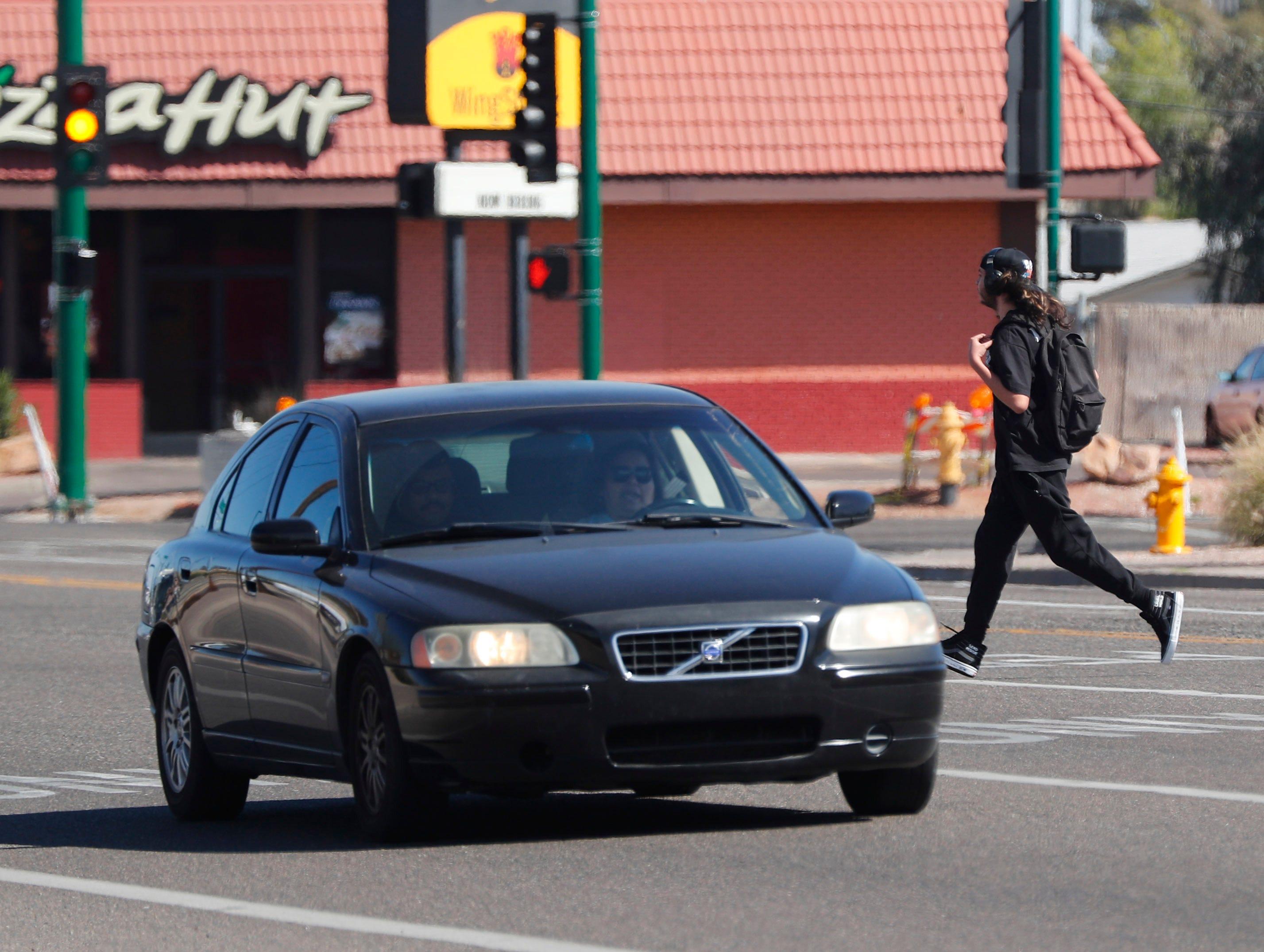 A pedestrian crosses Indian School Road west of 19th Avenue in Phoenix on March 10, 2019.