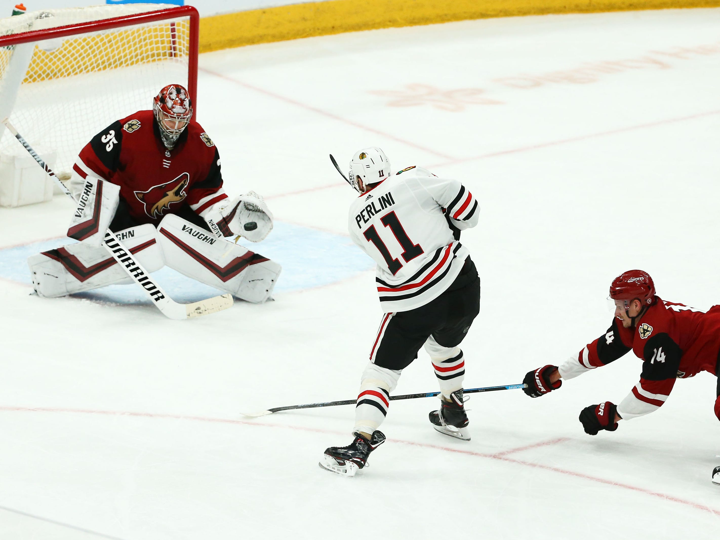 Arizona Coyotes goaltender Darcy Kuemper (35) makes a save on a shot by Chicago Blackhawks left wing Brendan Perlini (11) in the third period on Mar. 26, 2019, at Gila River Arena in Glendale, Ariz.