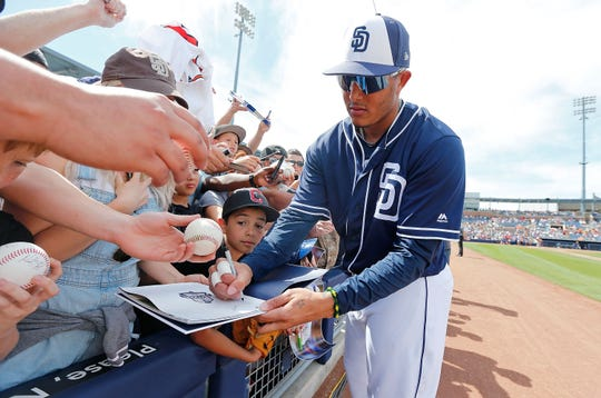 Manny Machado, estrella de los Padres, firma autógrafos a la gente.