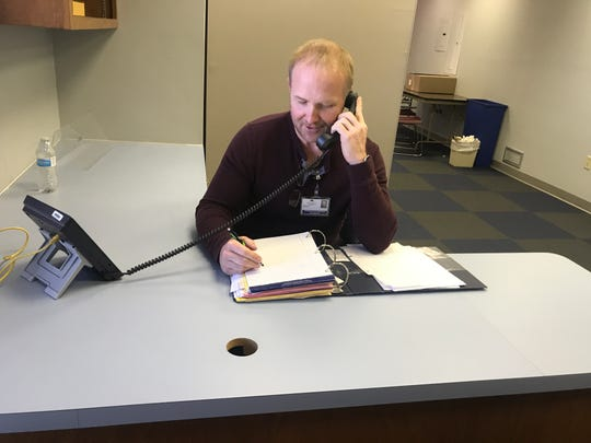 Howie White Jr. answers a phone in the Lebanon County Crisis Intervention office.