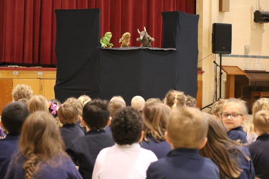 """Terri Winke and Jennifer Buch of Ida Rupp Public Library help kick off Immaculate Conception School's """"Literacy Day"""" celebration with a puppet show on Wednesday."""