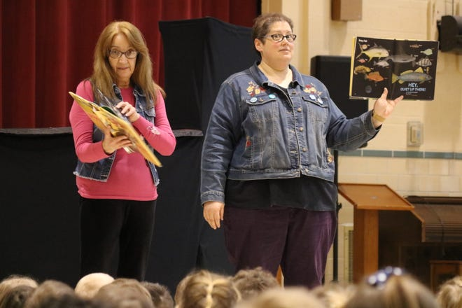 """Terri Winke and Jennifer Buch of Ida Rupp Public Library help kick off Immaculate Conception School's """"Literacy Day"""" celebration on Wednesday by reading selections from a children's poetry book."""