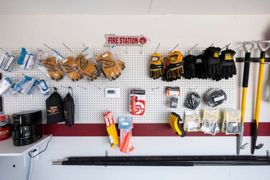 Gloves and other firefighting equipment hangs on a display rack inside The Fire Depot in Port Huron Township.