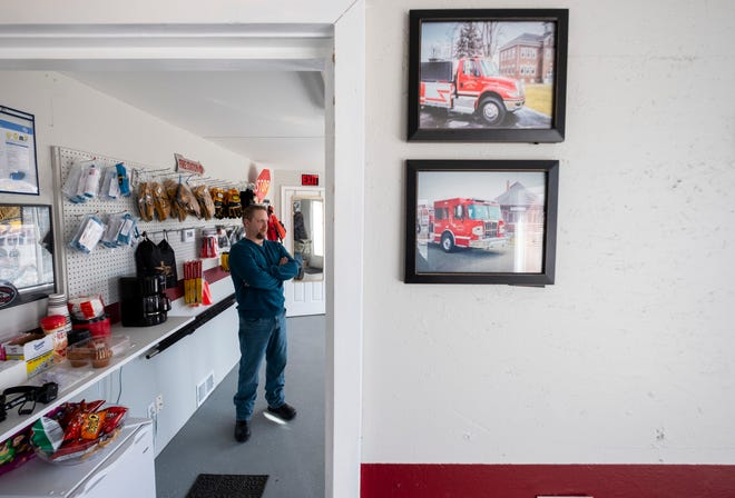 Two photos of firetrucks sold by Mussey Township Firefighter John Grzyb, pictured, hang on the wall inside his store, The Fire Depot, in Port Huron Township. Grzyb recently opened the store to sell firefighting equipment, including trucks, to local departments.