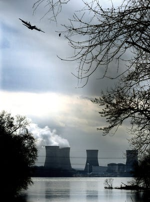 A military aircraft flies near the Three Mile Island Nuclear Generating Station viewed from the borough of Royalton, Dauphin County, Friday, March 15, 2019. The plant's Unit 2 reactors have been shut down since the March 28,1979, partial meltdown. Bill Kalina photo