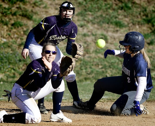 Eastern York's McKenzie Buchmyer watches as teammate Katie Lehman takes the throw as Dallastown's Allison Hoffman advances to third base during softball action at Eastern Wednesday, March 27, 2019. Bill Kalina photo