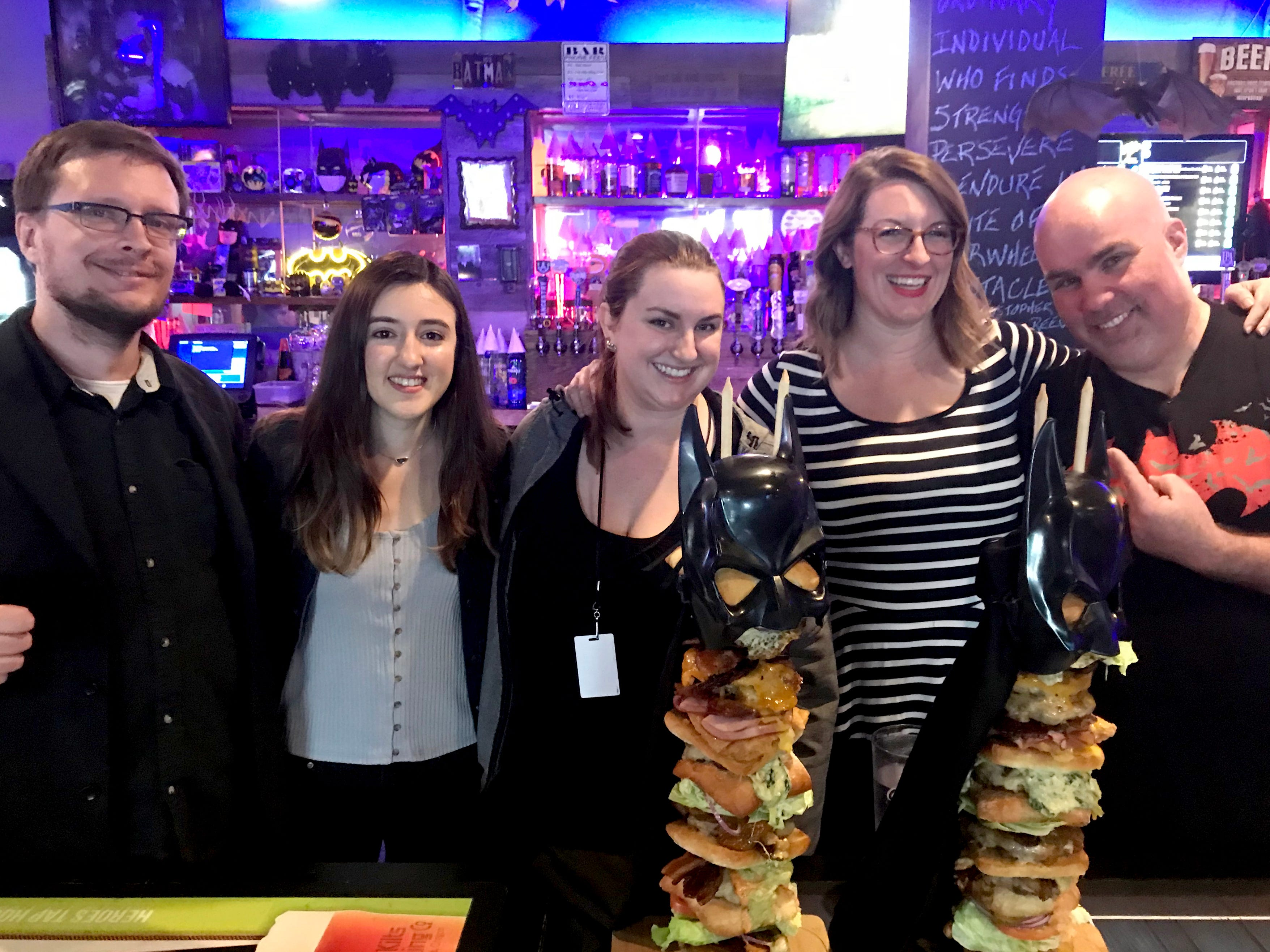 "Statesman Journal reporters, from left, state government reporter Ben Botkin, breaking new reporter Virginia Barreda, photojournalist Anna Reed and food and drink reporter Emily Teel go up against competitive eater ""Max Carnage"" during a Statesman Journal eating challenge to finish the Dark Knight Burger, consisting of six top-selling burgers, at Heroes Tap House in Salem on March 22, 2019. The Statesman Journal crew finished the stack in 35 minutes."
