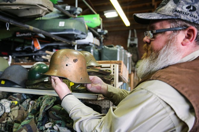 Taylor Cole looks over a military helmet Thursday, March 21, 2019, at Cole's Army Surplus.