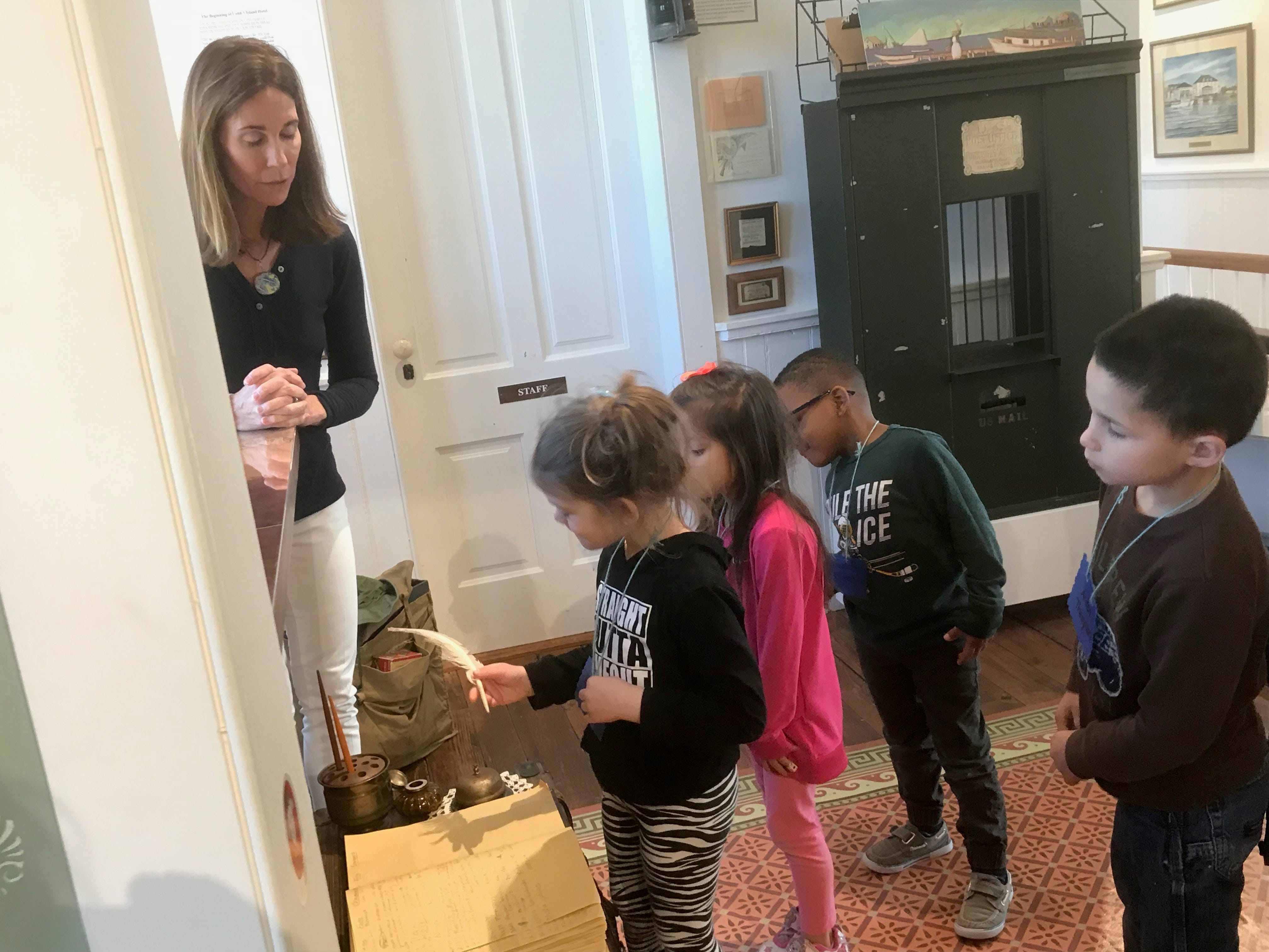 "A student ""checks in"" at the Cobb's Island Hotel exhibit as education director Sally Dickinson looks on, during a My First Field Trip event with Occohannock Elementary School pre-kindergarten students on Tuesday, March 26, 2019  at the Barrier Islands Center in Machipongo, Virginia."